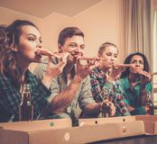 Multi-ethnic friends with pizza and bottles of drink Stock Image