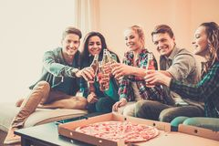 Multi-ethnic friends with pizza and bottles of drinks Stock Image