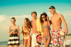 Multi ethnic friends relaxing on a beach Stock Images