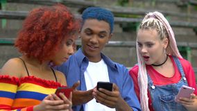 Multi-ethnic friends scrolling social networks, blue-haired guy sharing app news. Stock footage stock video footage