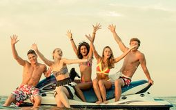 Multi ethnic friends sitting on a jet ski Royalty Free Stock Photos