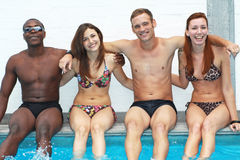 Multi-ethnic friends sitting on side of pool Royalty Free Stock Images