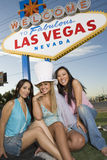 Multi Ethnic Friends Sitting Together. Portrait of multi ethnic friends sitting together against 'Welcome To Las Vegas' sign Royalty Free Stock Photography