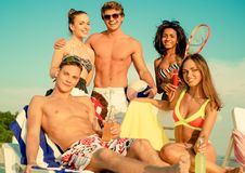 Multi ethnic friends sunbathing on a beach Royalty Free Stock Images