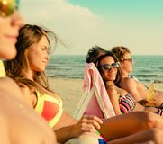 Multi ethnic friends sunbathing on a beach Royalty Free Stock Image