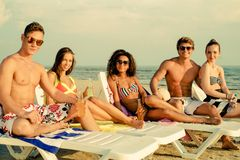 Multi ethnic friends sunbathing on a beach Stock Photography