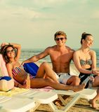 Multi ethnic friends sunbathing on a beach Stock Photos