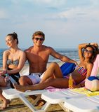Multi ethnic friends sunbathing on a deck chairs Royalty Free Stock Photos