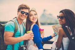 Multi-ethnic friends tourists  in a city. Multi-ethnic friends tourists with map and coffee cups near river in a city Stock Photo