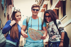 Multi ethnic friends tourists with map in old city Royalty Free Stock Photo