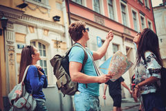 Multi ethnic friends tourists with map in old city Stock Photos