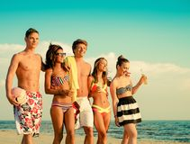Multi ethnic friends walking on a beach Royalty Free Stock Photos