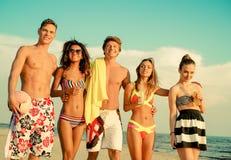Multi ethnic friends walking on a beach Royalty Free Stock Photo