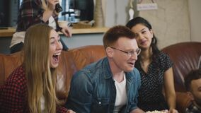 Multi-ethnic friends watch sports on TV. Slow motion. Fan supporters celebrate success with popcorn and drinks. Emotion. stock footage