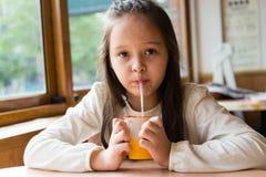 Multi-ethnic girl drinking juice Royalty Free Stock Image