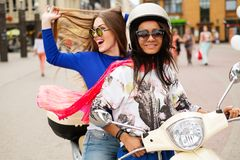 Multi ethnic girls on a scooter. In european city Stock Photos