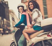 Multi ethnic girls on a scooter. In european city Stock Image