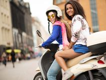 Multi ethnic girls on a scooter. In european city Royalty Free Stock Image