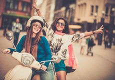 Multi ethnic girls on a scooter. In european city Stock Images