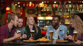 Multi-ethnic grappa friends sitting in a bar drinking beer and having fun chatting while eating chips.  stock video