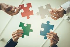 Multi-ethnic group of business professional putting four puzzle stock images