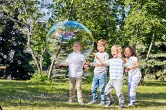 Having Fun with Soap Bubbles. Multi-ethnic group of children having fun with big soap bubbles while spending warm summer day at public park illuminated with Stock Photo