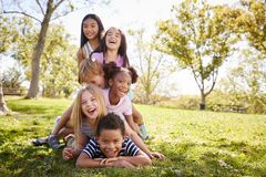 Multi-ethnic group of children lying in a pile in a park stock images