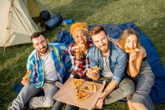 Friends eating pizza at the camping Stock Photo