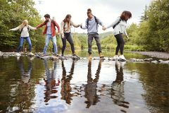 Multi ethnic group of five adult friends hold hands and help each other while carefully crossing a stream standing on stones durin. G a hike stock photo