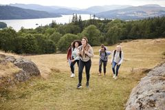 Multi ethnic group of five young adult friends hiking across a field uphill towards the summit, front view royalty free stock image
