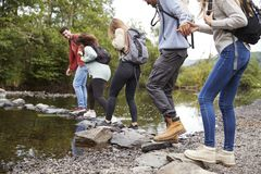 Multi ethnic group of five young adult friends hold hands walking on rocks to cross a stream during a hike, close up, back view stock photography