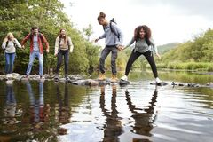 Multi ethnic group of five young adult friends laughing as they balance on rocks to cross a stream during a hike royalty free stock photography