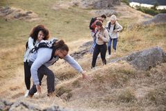 A multi ethnic group of five young adult friends smile while climbing to the summit during a mountain hike, close up stock photos