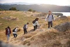 A multi ethnic group of five young adult friends smile while climbing to the summit during a mountain hike, side view stock photography