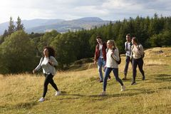 A multi ethnic group of five young adult friends smile while walking on a rural path during a mountain hike, side view stock photo