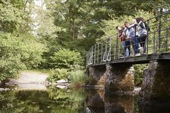 Multi ethnic group of five young adult friends stand looking down from a bridge during a hike royalty free stock image
