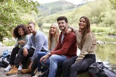 Multi ethnic group of five young adult friends taking a break sitting on rocks by a stream during a hike, portrait