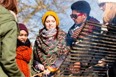 Multi-ethnic group of five young people having fun at barbecue. In winter Royalty Free Stock Photos