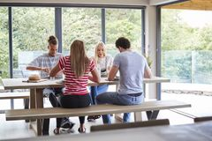 Multi ethnic group of four young adult friends eating at a casual dinner party in a modern dining room stock photo