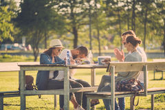 Multi-ethnic group of friends chatting in a park Stock Photos