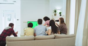 Multi ethnic group of friends chatting while sitting on the sofa in a spacious living room and watching a football match. They happy and excited at the end stock video footage