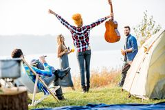Friends during the outdoor recreation. Multi ethnic group of friends dressed casually having fun during the outdoor recreation at the camping near the lake Stock Photography