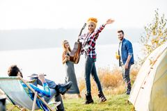 Friends during the outdoor recreation. Multi ethnic group of friends dressed casually having fun during the outdoor recreation at the camping near the lake Royalty Free Stock Images