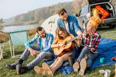 Friends during the outdoor recreation. Multi ethnic group of friends dressed casually having fun playing guitar during the outdoor recreation with tent, car and Royalty Free Stock Images