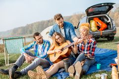 Friends during the outdoor recreation. Multi ethnic group of friends dressed casually having fun playing guitar during the outdoor recreation with tent, car and Stock Image