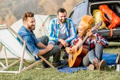 Friends during the outdoor recreation. Multi ethnic group of friends dressed casually having fun playing guitar during the outdoor recreation with tent near the Royalty Free Stock Images