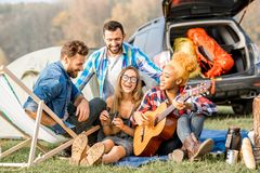Friends during the outdoor recreation. Multi ethnic group of friends dressed casually having fun playing guitar during the outdoor recreation with tent near the Royalty Free Stock Photography