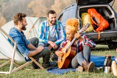 Friends during the outdoor recreation. Multi ethnic group of friends dressed casually having fun playing guitar during the outdoor recreation with tent near the Royalty Free Stock Photos