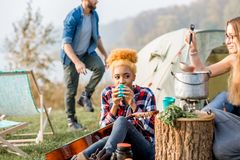 Friends during the outdoor recreation. Multi ethnic group of friends dressed casually having a picnic, cooking soup with cauldron during the outdoor recreation Stock Image