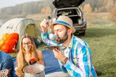 Friends during the outdoor recreation. Multi ethnic group of friends dressed casually having a picnic, cooking soup with cauldron during the outdoor recreation Royalty Free Stock Image